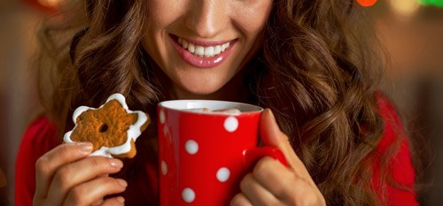 Woman smiling, eating cookie, and drinking cocoa out of a red mug