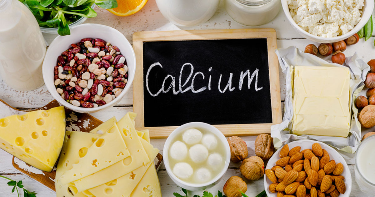 Different food sources of calcium, such as almonds and milk, surroundig a chalkboard that reads 'Calcium'